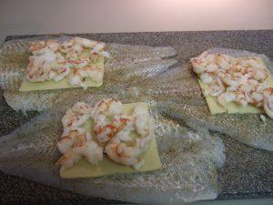 Place Split Cooked Shrimp on Flounder